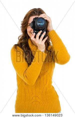 Woman photographing with camera on white background