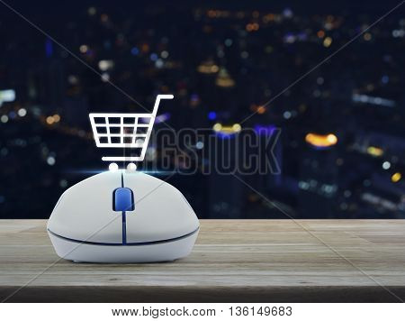 Wireless computer mouse with shopping online icon on wooden table in front of blurred light city tower Shopping online concept