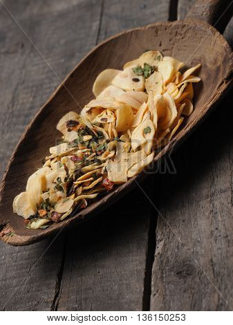 Old used wooden shovel with dried garlic and spicy herbs cooking ingredients concept image