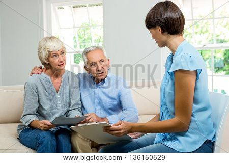 Consultant talknig with senior couple while sitting on sofa at home