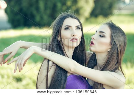 young pretty women with long windy hair in elegant violet dresses sunny day on green grass natural background
