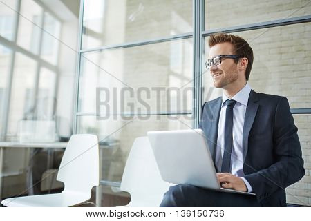 Businessman sitting with laptop in office and smiling