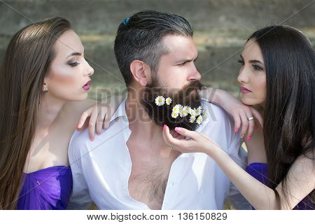 handsome man in white shirt with dandelion flowers in beard with two young pretty women in violet dresses on stony stairs sunny day outdoor