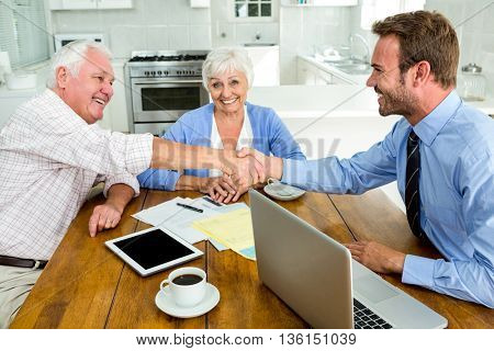 Happy senior man handshaking with agent while sitting at table in home