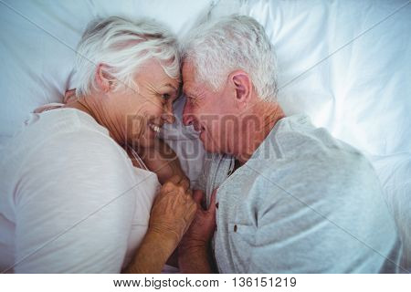 High angle view of senior couple touching head while lying on bed in room