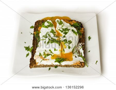 A poached egg freshly cooked and cut on a piece of rye toast with fresh herbs on top on a white plate on white background