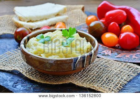 Eggplant dip in bowl with grape tomatoes in rustic table setting.