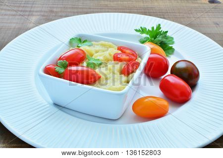 Eggplant dip in white bowl with cherry tomatoes.