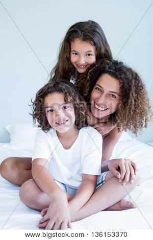Portrait of mother and children sitting together on bed in bedroom