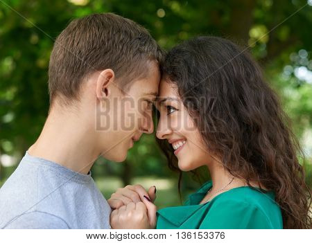 Romantic couple portrait posing in city park, summer season, lovers boy and girl