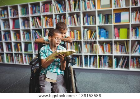 Little boys reading a book in the library