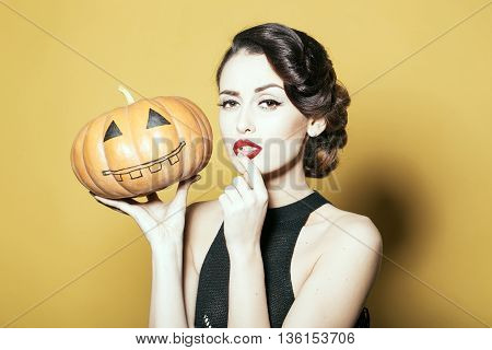 Serious woman with beautiful face and retro hairdo and red lips holding pumpkin in studio on yellow background. Halloween concept