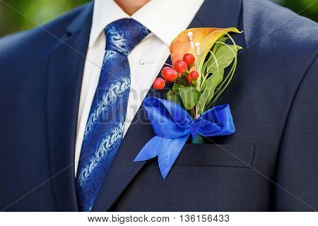 dark blue jacket of the groom and a beautiful boutonniere