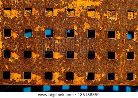 Plate metallic rusty with square holes slots perforated sheet shield screen on metallized background