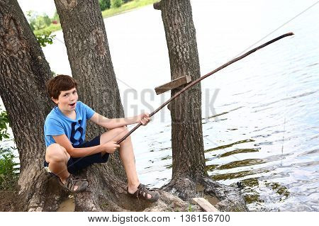 preteen handsome boy with fishing self made rode on the summer lake background close up photo