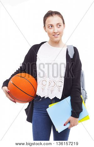 Cute student girl holding colorful notebooks and a basketball, isolated on white background