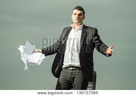 handsome tired male businessman in black formal jacket and white shirt with paper near leather arm chair outdoor on cloudy sky background