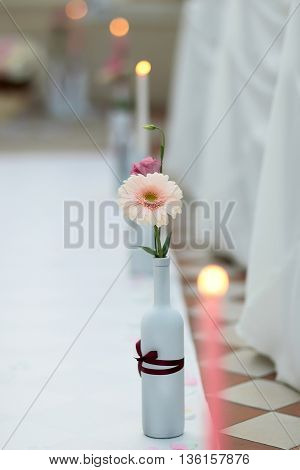 Beautiful flowers in white bottle decoration for wedding ceremony on tile floor on bokeh background