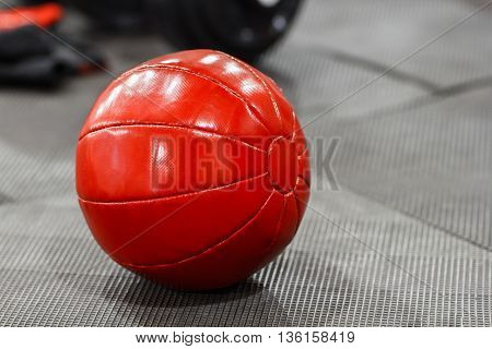 Red medicine weight ball on gym floor closeup. Weighted ball for doing fitness lying on the floor. Front view on red medicine ball in gym interior