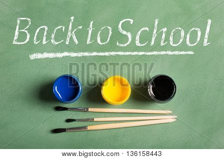 Paintbrushes and paints on a green chalkboard (top view). Back to school concept