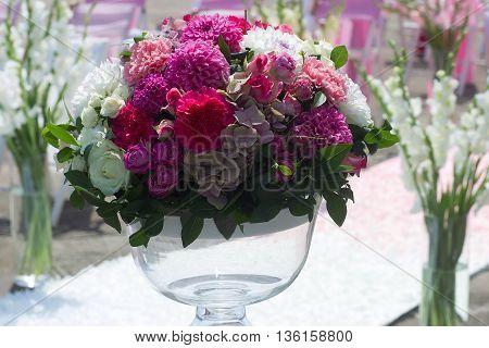Fresh flower arrangement in vase for wedding reception on blurred background