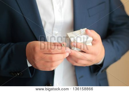 Groom holds gold wedding ring and jewelry gift box on blurred background
