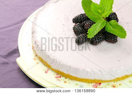 Homemade violet mulberry cheesecake with ment on violet board.