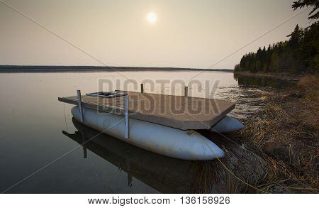 Pontoon boat tied up on shore as the sun rises behind