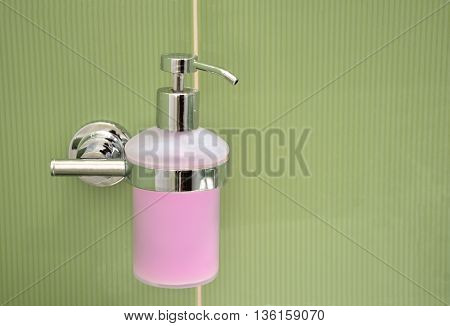 Soap container filled with purple foam fixed to green tile at wall in bathroom