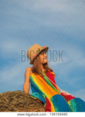 Little girl in a smart hat and bright dress sitting on a haystack on blue sky background