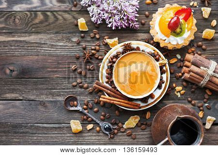 Rustic wooden background with cup and cezve of coffee fruit tart and lilac flowers. White vintage dinnerware and spoon. Breakfast at summer morning. Top view place for text.