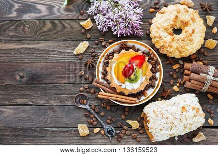 Rustic wooden background with different pastries - peanut and fruit tarts marzipan bun. Different spices - cinnamon walnuts peanuts ginger. Top view of tasty desserts. Place for text.