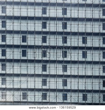 Close-up fragment of the facade of a modern building with large glass windows. Modern architecture. Modern industrial building with glass. Exterior of a multistory building.