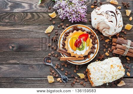 Rustic wooden background with different pastries - chocolate meringue fruit tart marzipan bun. Different spices - cinnamon walnuts peanuts ginger. Top view of tasty desserts. Place for text.