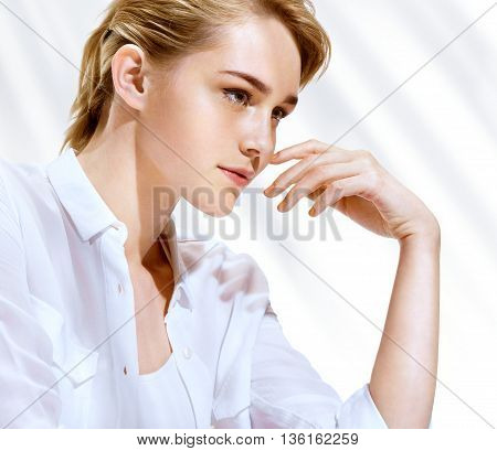Beautiful blonde in white blouse. Close up of an attractive girl of European apperance in sanny glow.
