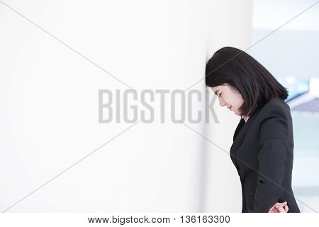 Unhappy thinking business woman with white wall background great for your design or text asian