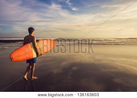 Sun surfer. A man is walking with a surf in his hands across the ocean shore.