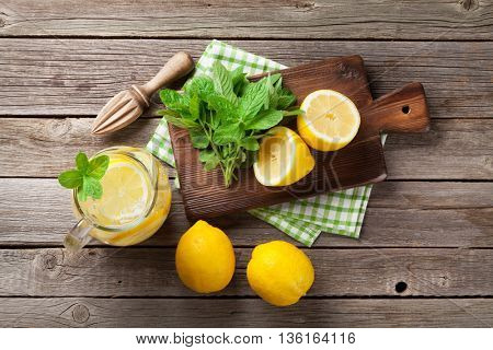 Lemonade pitcher with lemon, mint and ice on garden table. Top view