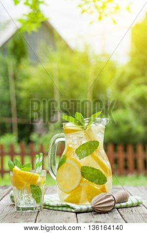 Lemonade with lemon, mint and ice on garden table. View with copy space
