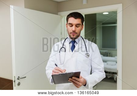 medicine, healthcare and people concept - doctor writing to clipboard at hospital