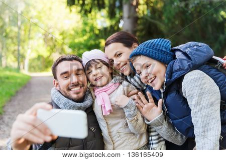 technology, travel, tourism, hike and people concept - happy family with backpacks taking selfie by smartphone and hiking