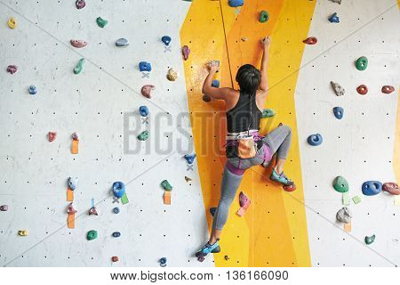Back view of sportswoman climbing in the gym