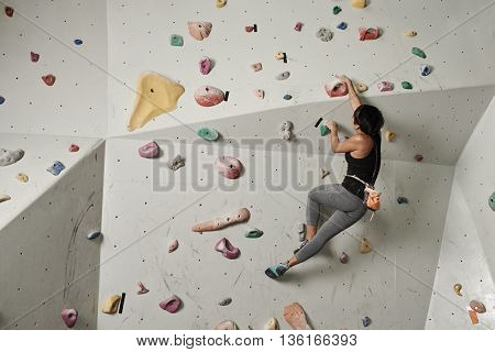 Girl climbing indoors, view from the back