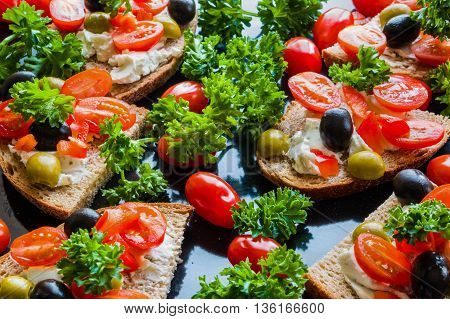 Bruschetta with green and black olives feta cheese cherry tomatoes parsley and red pepper on black background. Healthy snack breakfast brunch.