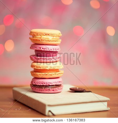 Colorful macaroons stay in stack on book closeup over christmas lights