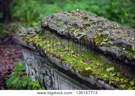 Old stone coffin with moss closeup selective focus