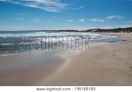 Glistening Indian Ocean waters at Blue Holes Beach with sand and coastal dunes under a blue sky in Kalbarri, Western Australia.
