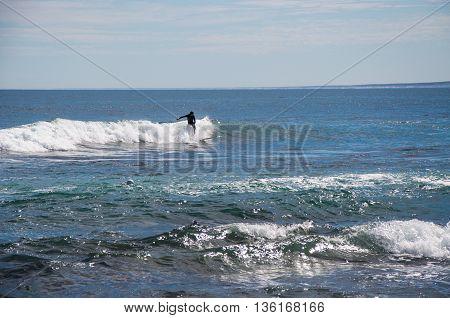 KALBARRI,WA,AUSTRALIA-APRIL 23,2016: Surfer in the foamy Indian Ocean waves at Blue Holes Beach under a clear sky in Kalbarri, Western Australia.