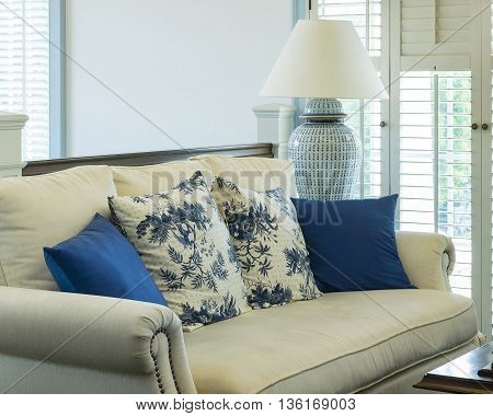 luxury living room with blue pattern pillows on sofa and decorative table lamp
