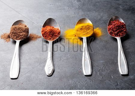 Colorful spices in spoons over stone table